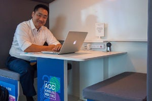ACC member at desk with laptop.